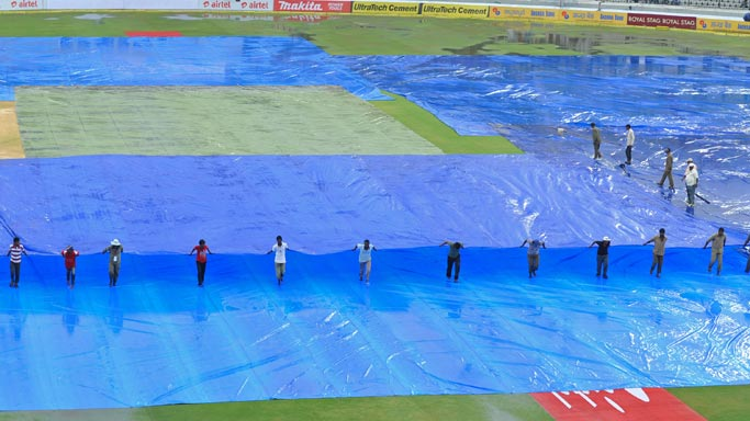 Groundsmen-cover-the-pitch-with-tarps-as-rain-stops-play-during-the-third-day-of-the-first-Test-match-between-India-and-New-Zealand
