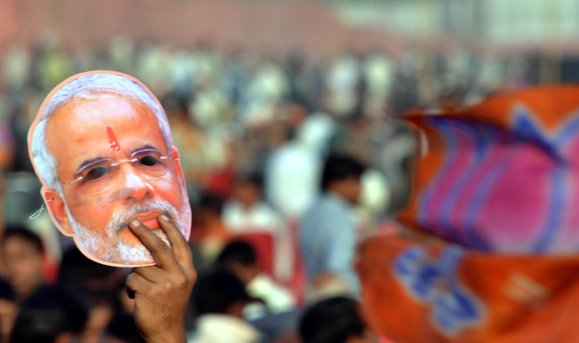 A-Narendra-Modi-supporter-holds-a-mask-of-the-BJP