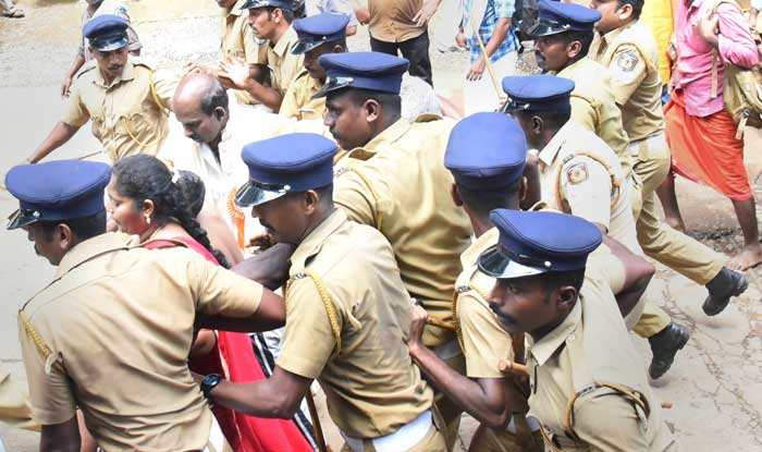 Police escort Madhavi (of Andhra Pradesh) and her family members after she was heckled by the protesters