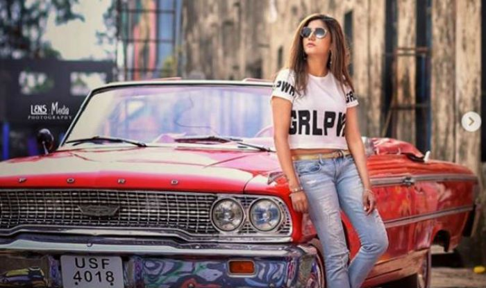 Haryanvi Dancer Sapna Choudhary Looks Hot Yet Sexy in a White Crop Top And Blue Jeans as She Poses With a Red Car