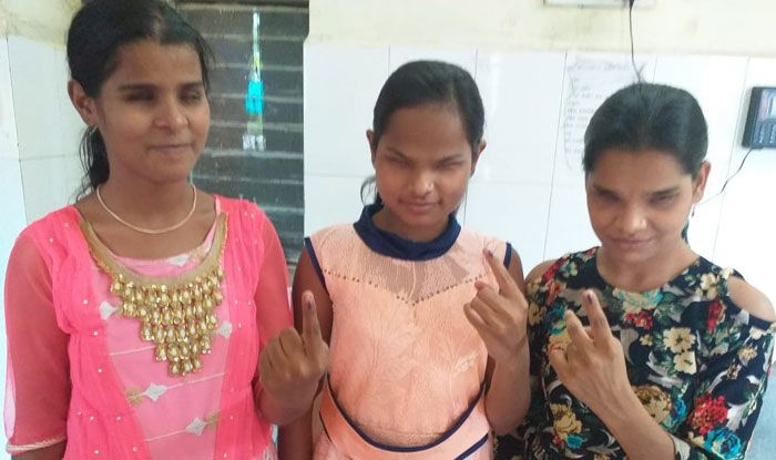 Visually challenged voters show their inked fingers