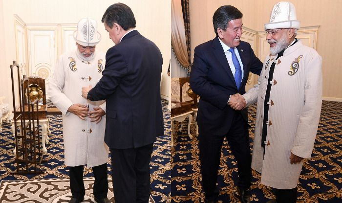 Kyrgyzstan President Jeenbekov gifts PM Modi a traditional Kyrgyz hat and coat. Photo Courtesy: IANS